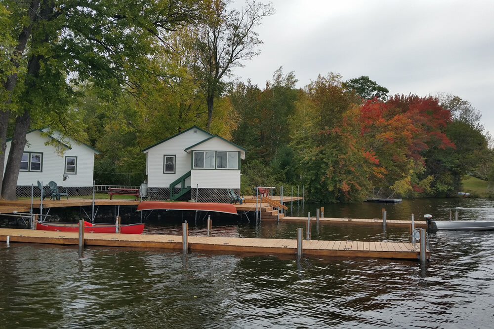 red and orange leaves show the start of fall behind cabins 1 and 2 with boat dock in front