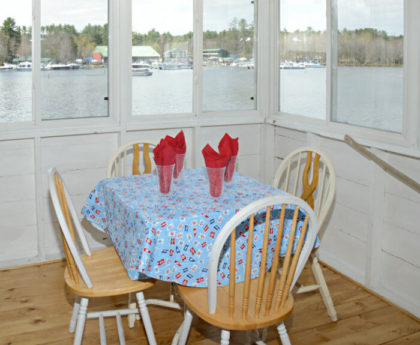 dining table set with blue cloth and red napkins on porch overlooking water