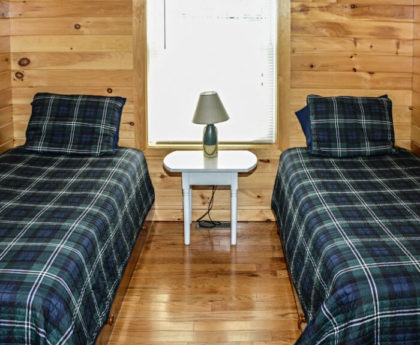 two twin beds with blue and green plaid covers, knotty pine walls