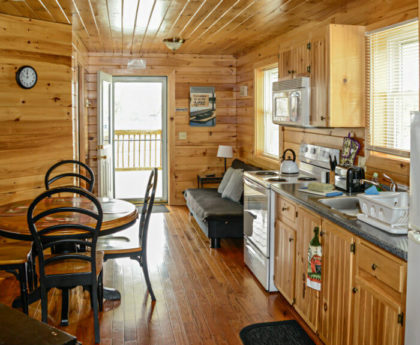long view of kitchen with white appliances, round dining table, and small couch, knotty pine on walls, ceiling and floors, door open to porch at far end