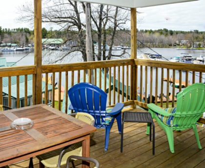 views of water, boats and trees from second story covered porch with corner of dining table, one blue and one green lounge chair
