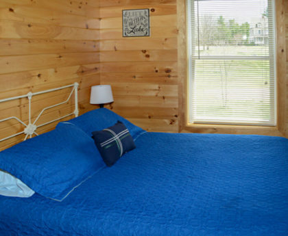 side view of queen bed with vibrant blue cover, knotty pine walls and brightly lit window showing adjacent farmhouse in distance