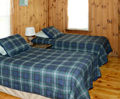 twin beds with tartan covers, knotty pine walls