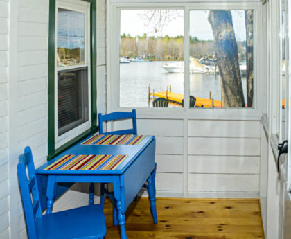 blue table and chairs in front of a window on porch with water views beyond