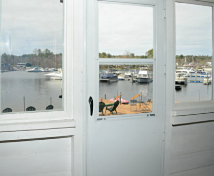 view of water, boats and marina through white storm door in center and windows on each side