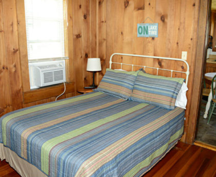 double bed with striped multi colored spread, white iron headboard and small lamp to the side