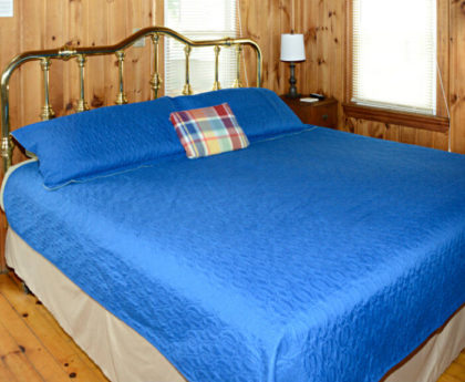 large king bed with vibrant blue cover and brass headboard, knotty pine walls