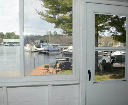 views of water, boats, marina and pine tree through white porch door and window