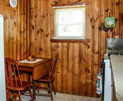 drop-leaf wood table and chairs in corner of kitchen with knotty pine walls