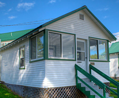 front exterior view of white cabin with green roof, stairs leading up to enclosed porch entrance