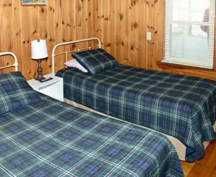 two twin beds with blue green plaid covers, white iron headboards, knotty pine walls