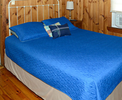 large bed with vibrant blue cover, white iron headboard, knotty pine walls