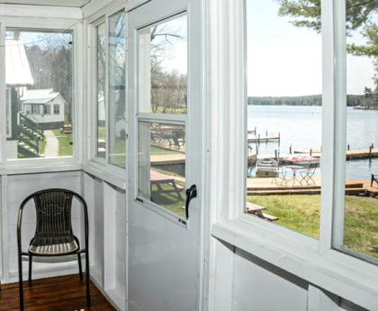 views of water, boats and distant skyline through porch windows and door, one chair in corner
