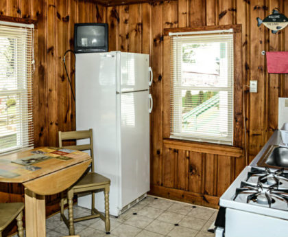 kitchen with white refrigerator in corner, wood table and chairs, knotty pine walls and brightly lit window