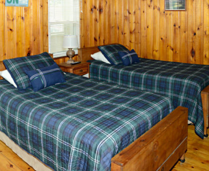 twin beads with green and blue plaid covers, wood footboards, knotty pine walls