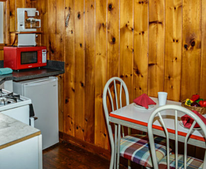 kitchen table and chairs, bright red microwave oven on corner of counter above refrigerator