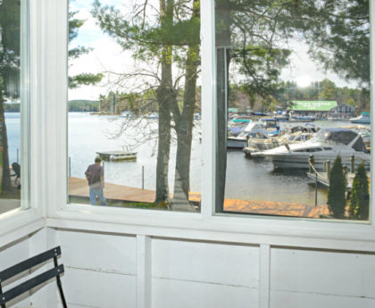 views of docks, boats, water and pine tree through porch windows