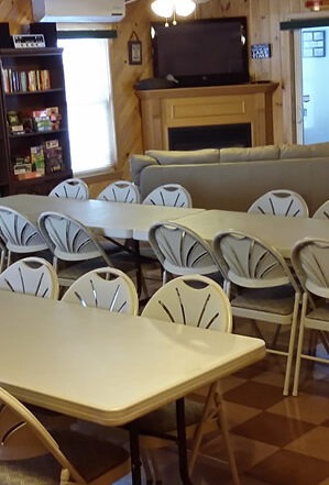 tables and chairs set for meeting in our pine paneled rental hall
