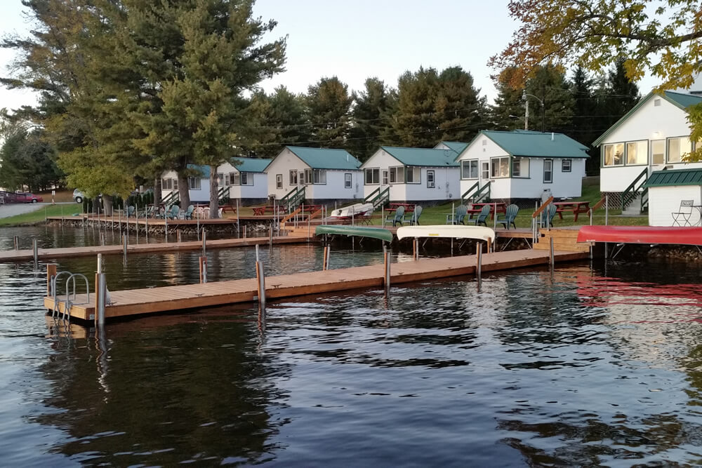 quaint row of white cabins with green metal roofs line the shore