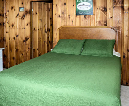 bed with forest green cover, wood headboard, knotty pine walls