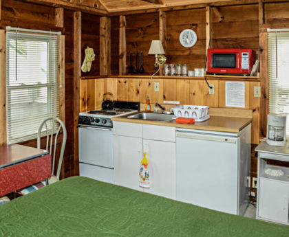 kitchen wall with white appliances, small red dining table, knotty pine walls
