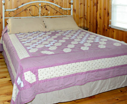 bed with lavender plaid cover, tan pillows and white iron headboard against knotty pine walls