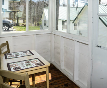 small table with placemats and two chairs on white painted porch with views of white cabins with green roofs and a section of woods