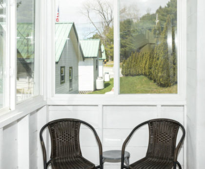 two brown chairs at end of a narrow porch with views of a row of white cabins and pine trees through porch windows