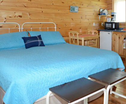 large bed with light blue cover and white iron headboard, knotty pine walls and small brown bench at foot of bed