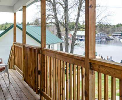 long view of porch with views of trees and water through wooden railings