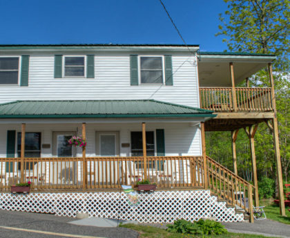 exterior of two story white building with green roof, covered porch on main level with flowerboxes and covered deck extending from right side on upper level