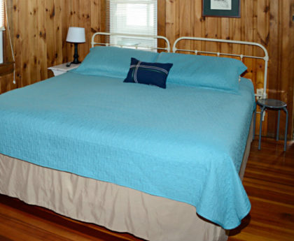 large bed with light blue cover and white iron headboard, knotty pine walls and a brightly lit window shown from bottom of bed