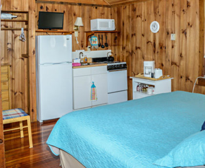 bottom edge of large bed with light blue cover, kitchen tucked into corner with white appliances, knotty pine walls