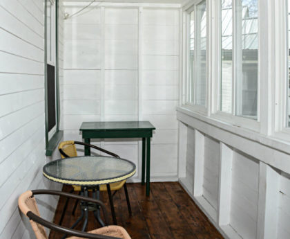 long view of narrow enclosed white porch with two cane chairs and round table facing windows