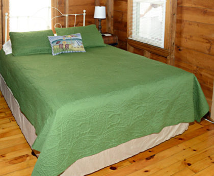 queen bed with forest green cover, white iron headboard, lamp and side table, knotty pine walls and floor