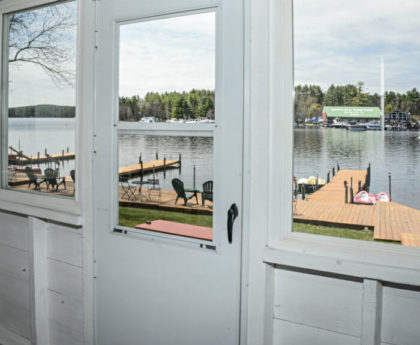 view of redwood docks, boats and water through white screen door and windows