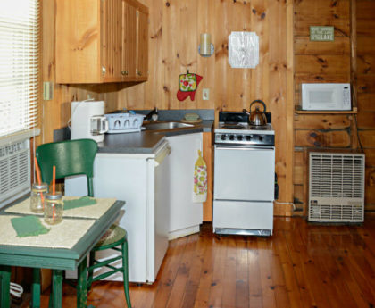 small kitchen with sink set into corner, refrigerator and green table and chair on left, stove, microwave and wall heater to right, knotty pine walls