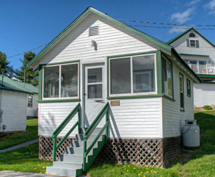 exterior front view of white cabin with green roof, stairs leading up to entry door flanked by several porch windows on each side