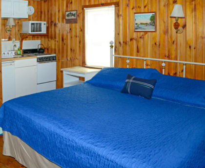 large bed with vibrant blue cover, decorative white metal headboard, small kitchen area with white appliances tucked into corner at back, knotty pine walls
