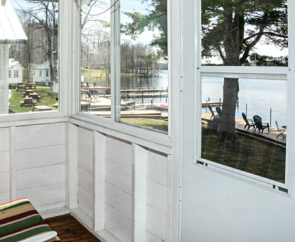 views of docks, boats, water and trees through white porch door and windows on a sunny day