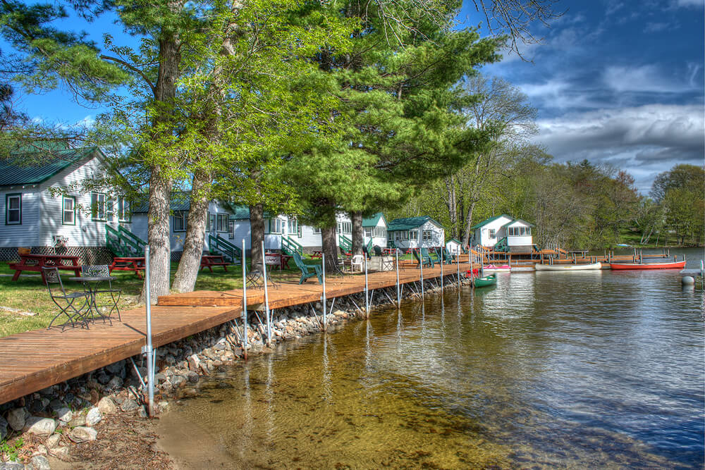 row of cabins and shoreline boat dock with pine trees and brilliant blue sky