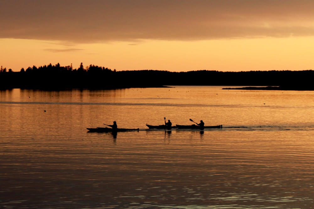 kayakers making their way across the pond as daylight fades