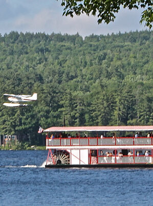 paddle wheeler boat taking passengers on an afternoon cruise as a seaplane passes