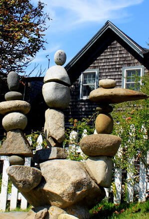 creative three-pronged rock sculpture in front yard of a weathered grey seaside cottage
