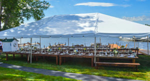 rows of tables set and decorated under white tent with blue water of pond behind