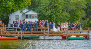 wedding party and guests on dock over water during ceremony with cabins and woods in background