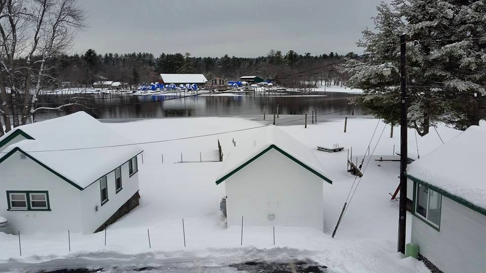 lots of white snow piled on cabin roofs at the edge of the pond